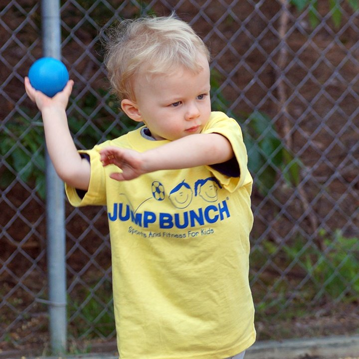 Blonde boy throwing blue ball