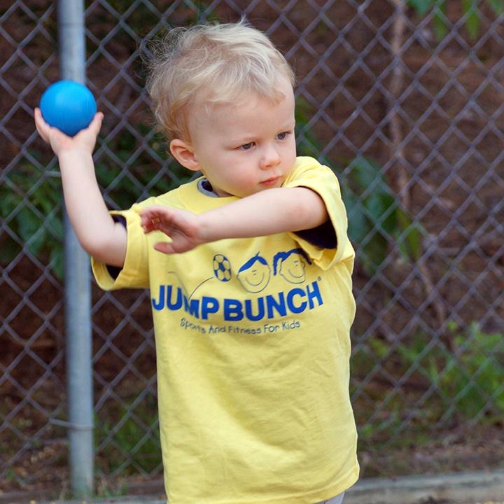 Blonde boy throwing blue ball